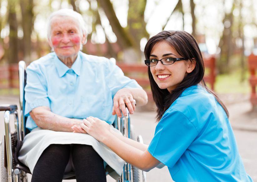 בית חולים גריאטרי - מטפלת במדים של מרכז גריאטרי או בית אבות יושבת ליד אישה במצב סיעודי ומחזיקה לה את היד