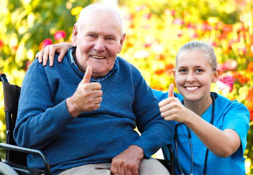 בית אבות סיעודי - אחות יושבת ליד איש קשיש על כסא גלגלים