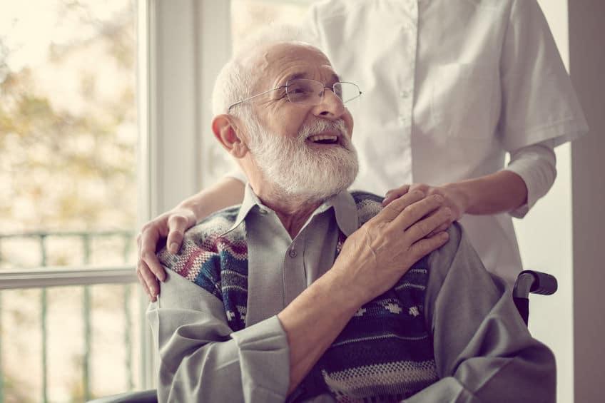 בתי אבות לתשושי נפש - איש זקן על כסא גלגלים מקבל טיפול ממטפלת בבית אבות