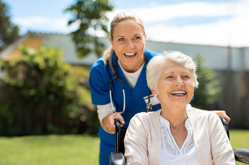 אחות מאושרת וקשישה יושבת בכיסא גלגלים נהנית מפגישה טיפולית באחד מבתי אבות במרכז ישראל