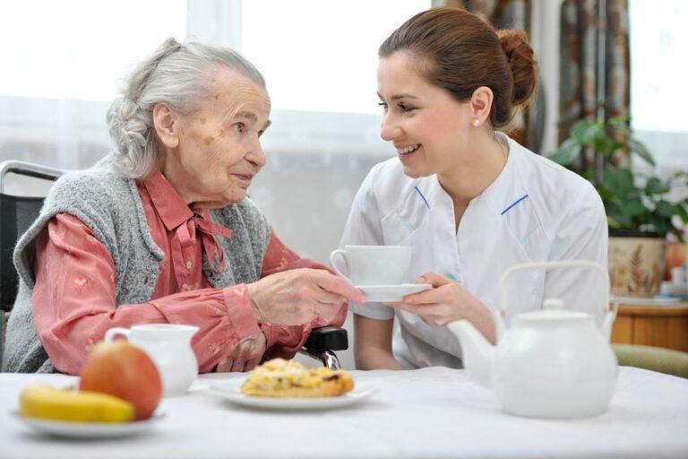 אחות בית אבות מגישה תה לקשישה