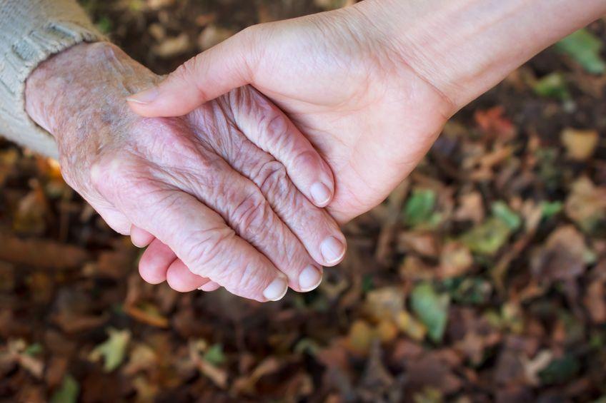 בעיות זקנה - מטפלת שמחזיקה את היד של זקנה בבית אבות במרכז