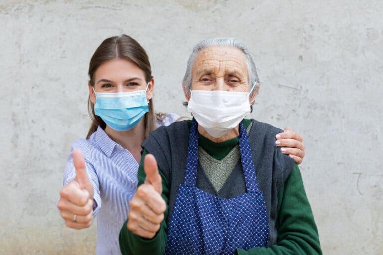 אישה זקנה בבית אבות חובשת מסכה עם המטפלת בתקופת הקורונה