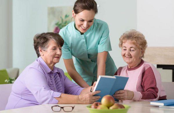 בתי אבות ברמת גן - שני נשים קשישות קןראות ספר בבית אבות שלידם עומדת מטפלת של המקום