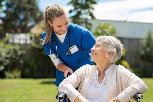 קשישה יושבת על כסא גלגלים באחד מבתי אבות בנס ציונה ואחות מסייעת לה