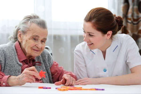 צוות רפואי בבתי אבות בנתניה משחקת עם אישה קשישה