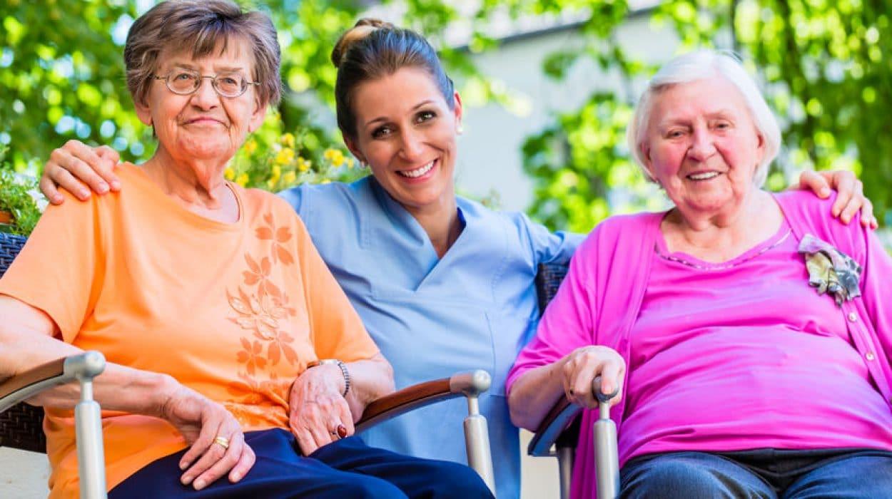 המטפלת יושבת עם שתי קשישות. המקום הינו בתי אבות בצפון - שתי הזקנות מחייכות ונראות מרוצות מהמקןם