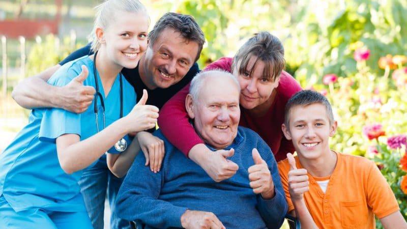 בית אבות לגיל השלישי - תמונה של קשיש יושב עם המשפחה שלו וצוות רפואי בבית אבות