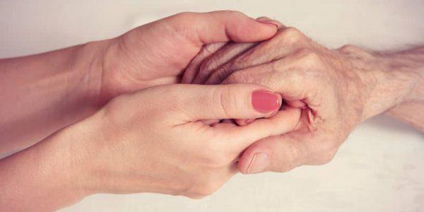בתי אבות בבני ברק - צוות רפואי מחזיק בידיים של אחד מהקשישים ומסייעת לו