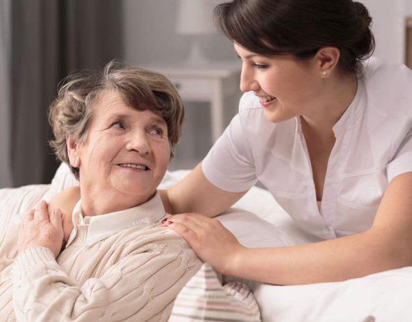 בתי אבות בתל אביב - אחות של בית אבות סיעודי שמה יד על הכתף של אישה זקנה שיושבת על הספה