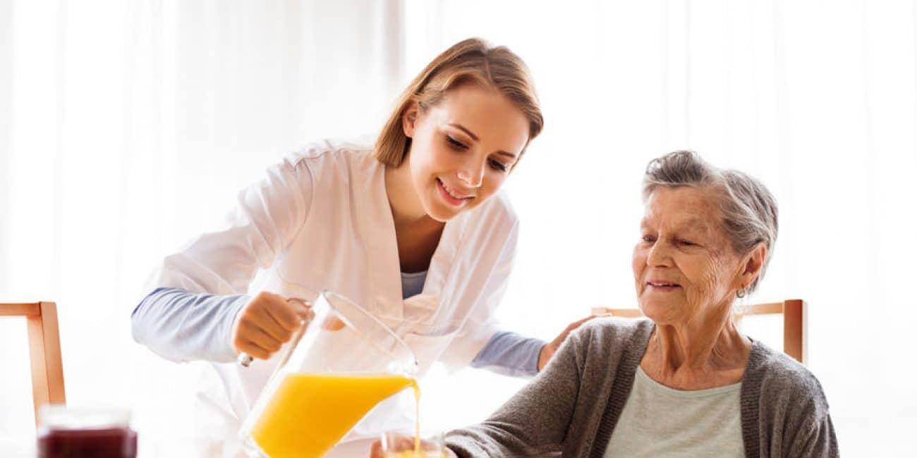 בתי אבות בשרון - מבקר בריאות ואישה בכירה במהלך ביקור בית. אחות ששפכה מיץ תפוזים לאישה מבוגרת